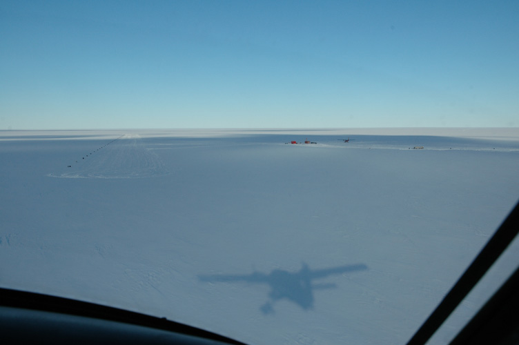 The plane rushes towards its shadow at the skiway