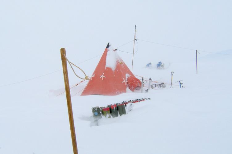 Snow drifting around a pyramid tent