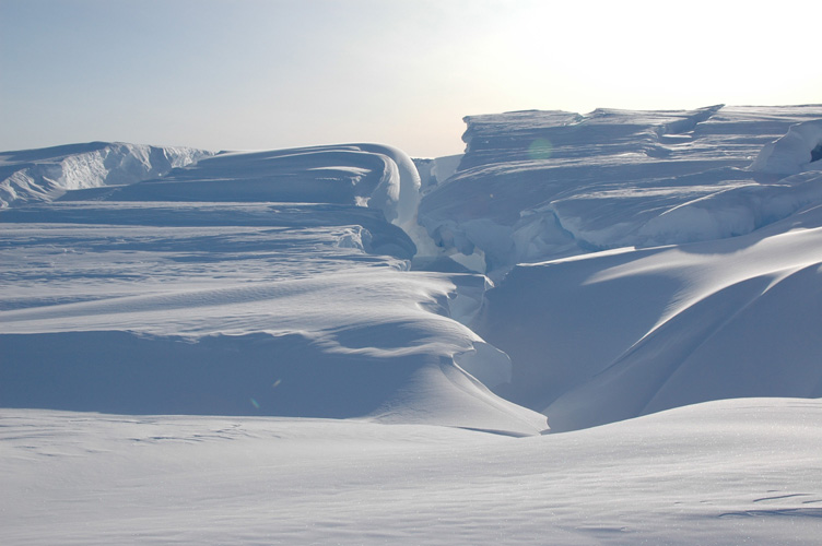 Folds of wind blown snow over huge crevasses