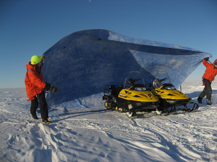 Throwing a tarp over the skidoos